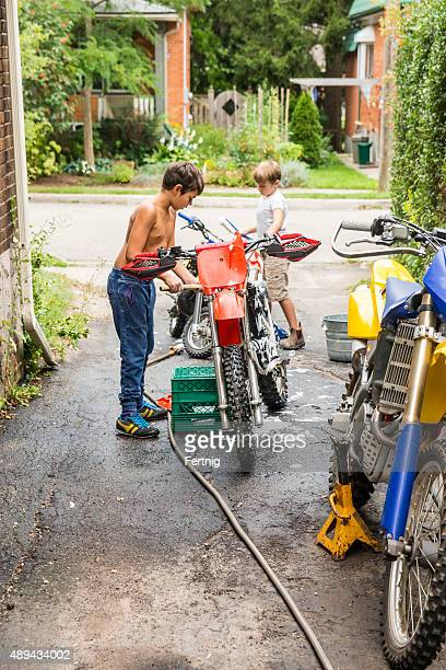 Two brothers cleaning their dirt bikes in the driveway.