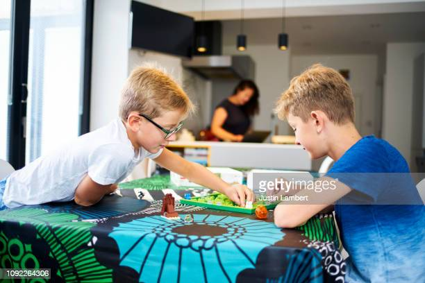 two brothers concentrating playing a board game on the kitchen table - saltdean stock pictures, royalty-free photos & images