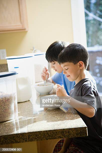 Two brothers (9-14) eating cereal in domestic kitchen, side view