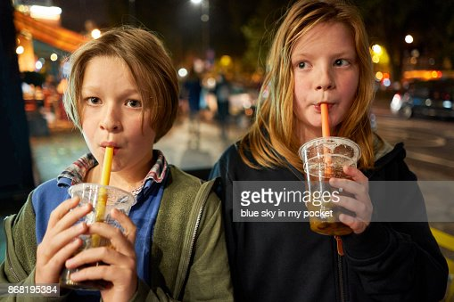 Two brothers enjoying a Bubble Tea at night.