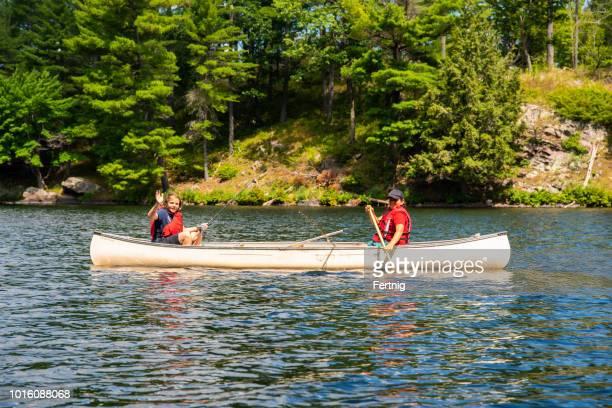 dos hermanos pescando en una canoa en un lago norte - life jacket photos fotografías e imágenes de stock