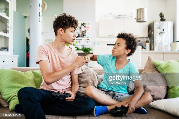 two brothers fist bumping while paling computer games - brother stock pictures, royalty-free photos & images
