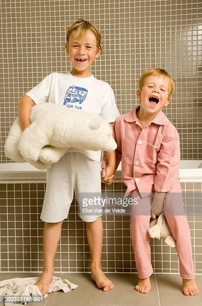 Two brothers (4-6) holding teddy bears beside bathtub, portrait