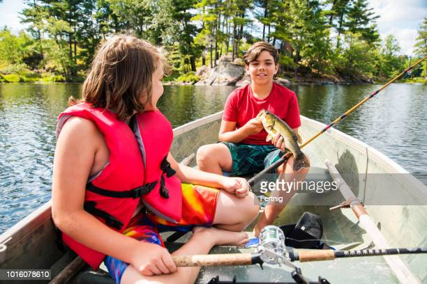 two brothers in fishing boat on beautiful northern lake holding a fish they caught. - largemouth bass stock pictures, royalty-free photos & images