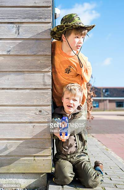 Two brothers in soldier's uniform play outside