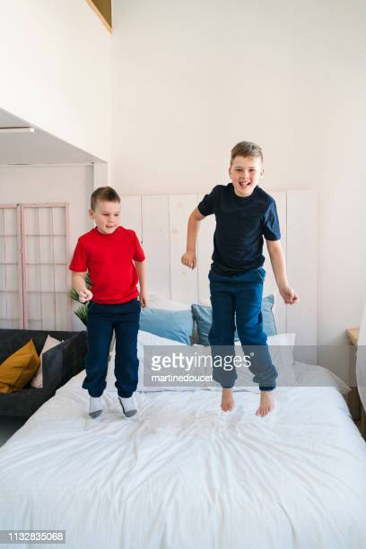 "two brothers jumping on a bed. - ""martine doucet"" or martinedoucet fotografías e imágenes de stock"