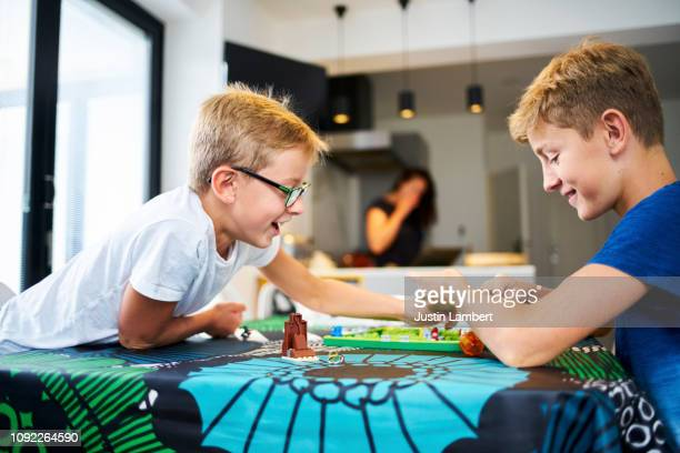 two brothers laughing playing a board game on the kitchen table - hermano fotografías e imágenes de stock