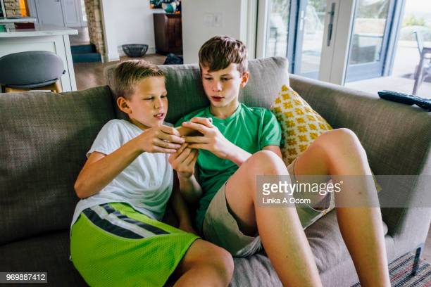 two brothers looking at smart phone on sofa - pantaloncini grigi foto e immagini stock