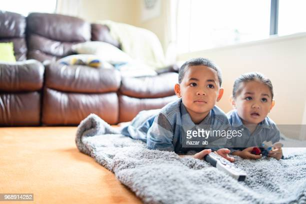 Two brothers lying down and watching TV.