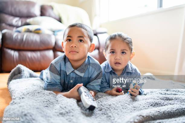 two brothers lying down and watching tv. - minority groups stock pictures, royalty-free photos & images