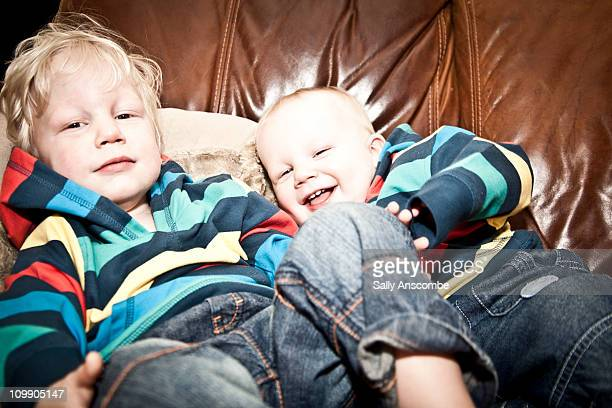 Two brothers lying on the sofa