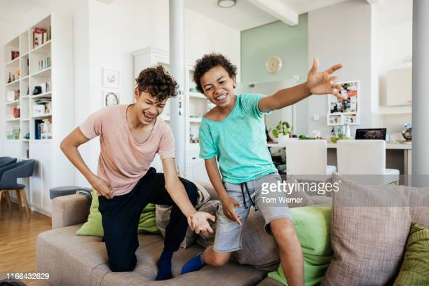 two brothers messing around having fun at home - pre adolescent child stock pictures, royalty-free photos & images