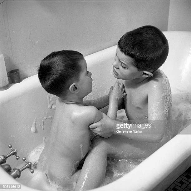Two brothers mock fighting in a bathtub