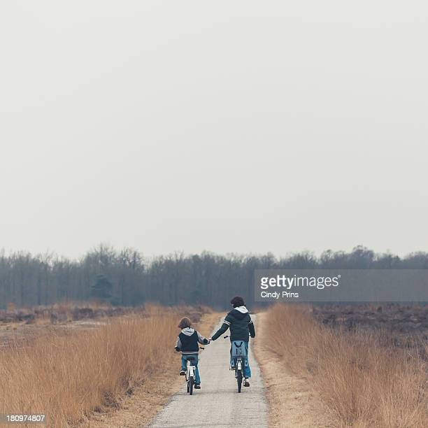 Two brothers on bicycles holding hands