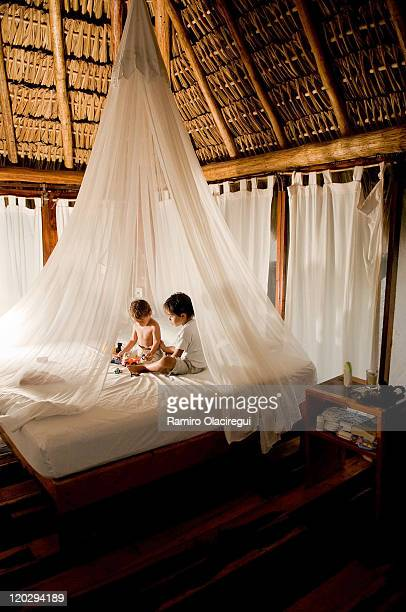 two brothers palying with toys on  bed - mosquito net stock photos and pictures