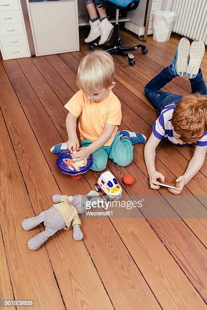Two brothers playing on floor of a workroom