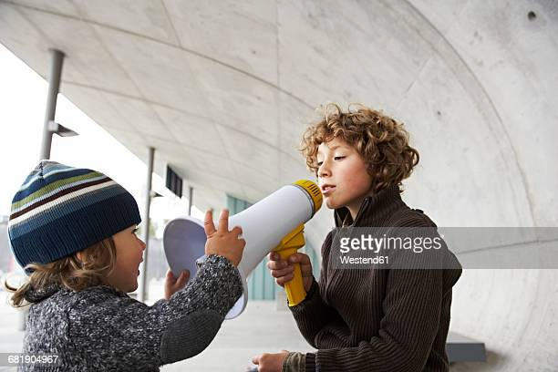 Two brothers playing with a megaphone