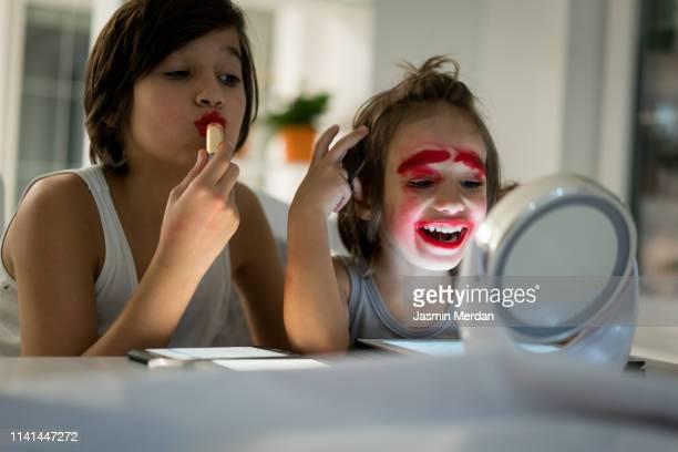 two brothers playing with lipstick on mirror - equidad de genero fotografías e imágenes de stock