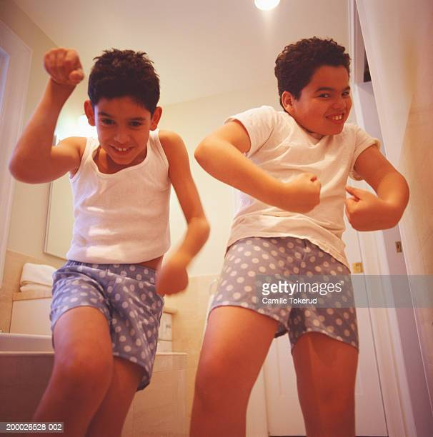 two brothers (10-13) posing, flexing muscles in bathroom - junge in unterhose stock-fotos und bilder