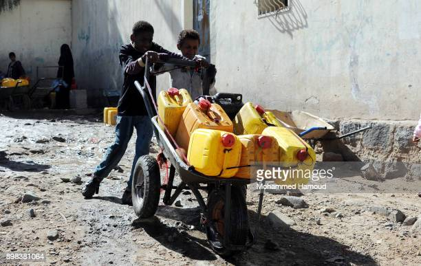 Two brothers push a wheelbarrow carrying jerry cans after they filled them with clean water from a charity water pump during a water shortage on...