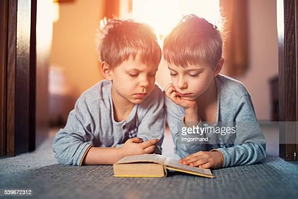 due fratelli leggendo un libro insieme nel mattino - fratello foto e immagini stock