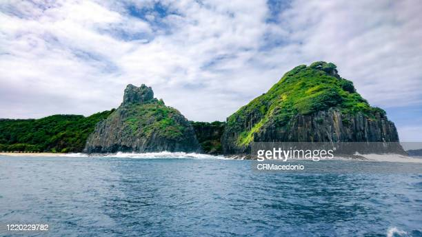 two brothers rock formation seen from the sea, fernando de noronha. - crmacedonio stock pictures, royalty-free photos & images