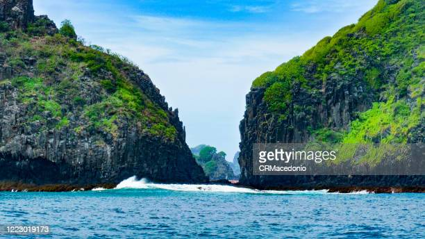two brothers rock formation seen from the sea, fernando de noronha. we can see the bay of pigs in the background. - crmacedonio - fotografias e filmes do acervo