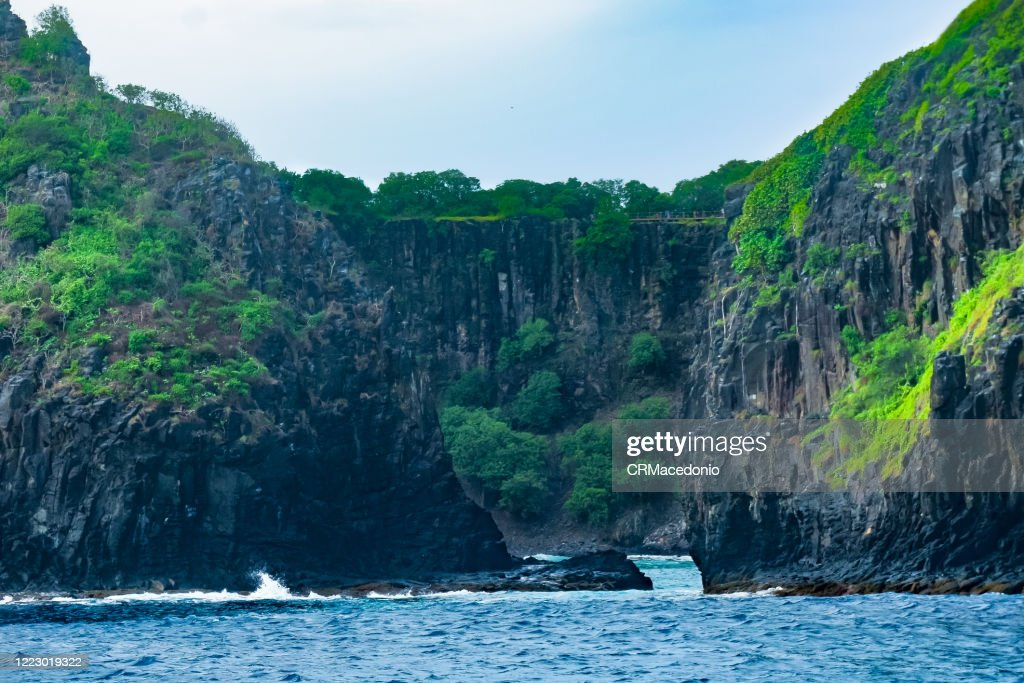 Two Brothers rock formation seen from the sea, Fernando de Noronha. We can see in the background the wall of Praia do Sancho. : Stock Photo