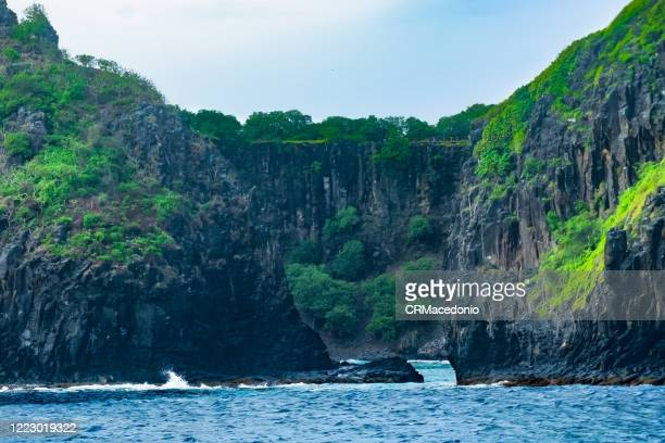 two brothers rock formation seen from the sea, fernando de noronha. we can see in the background the wall of praia do sancho. - crmacedonio stock pictures, royalty-free photos & images