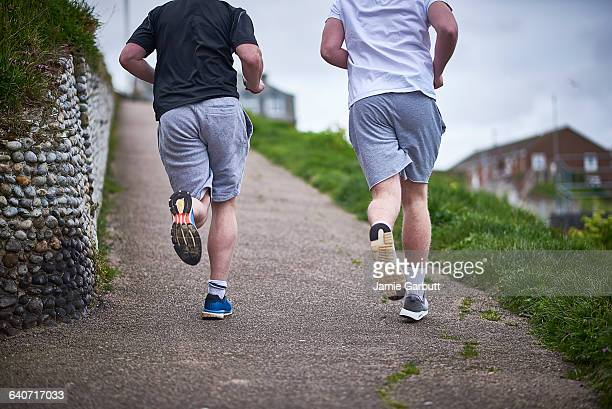 Two brothers running together up a slope