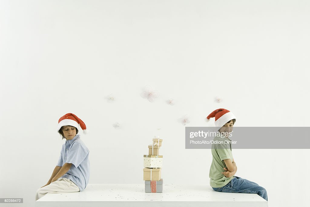 Two brothers sitting back to back, Christmas gifts stacked between them, both wearing Santa hats : Stock Photo
