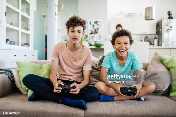 two brothers sitting on couch playing computer games - 12 13 jahre stock-fotos und bilder