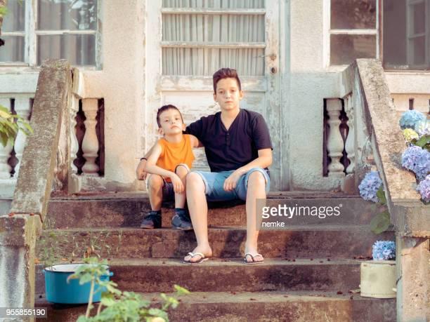 two brothers sitting outdoor - fratello foto e immagini stock