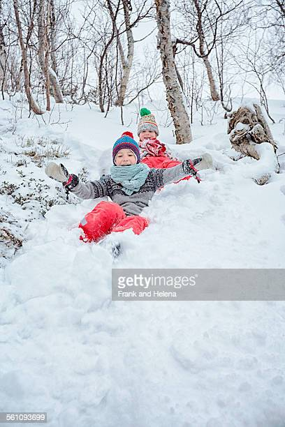 Two brothers sliding down snow covered hill, Hemavan,Sweden