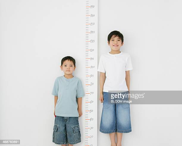 Two Brothers Standing Besides Scale