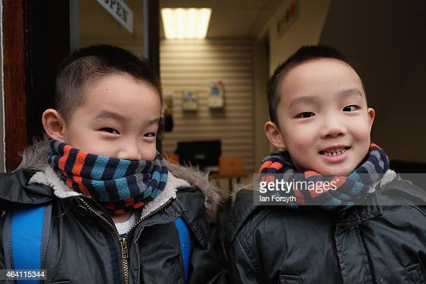 Two brothers standing in a doorway react to the camera as the Chinese community come together to welcome in the Chinese New Year on February 22 2015...