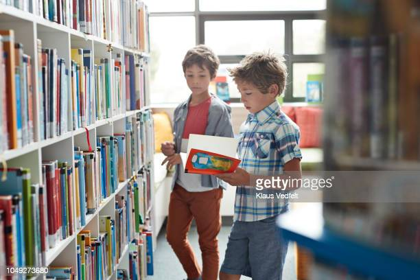 two brothers standing in school library - 綴り ストックフォトと画像