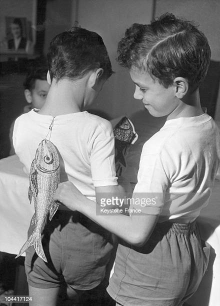 Two brothers sticking April Fool's Day fish on each other's back on April 1, 1963.