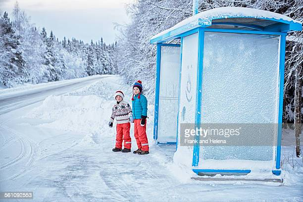 two brothers waiting at snow covered bus stop, hemavan,sweden - 6 7 jaar stockfoto's en -beelden