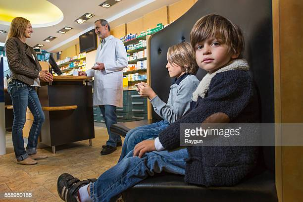 two brothers waiting whilst mother is talking to pharmacist in a drugstore - patients brothers stock pictures, royalty-free photos & images