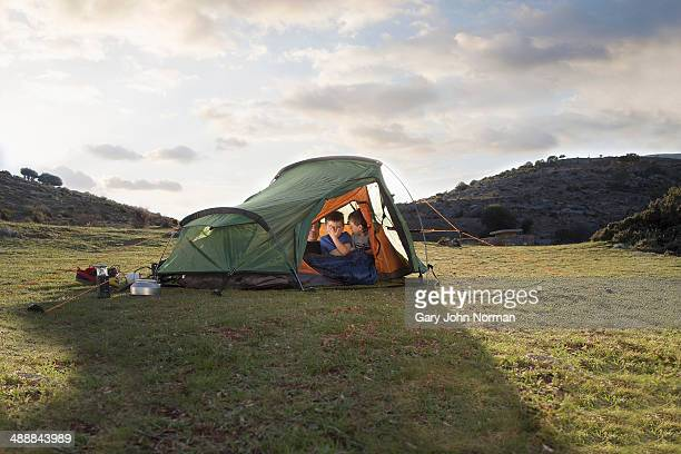 Two brothers waking up inside tent