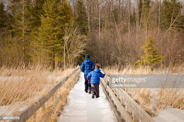"""two brothers walking on a boardwalk near a forest - """"danielle donders"""" stock pictures, royalty-free photos & images"""