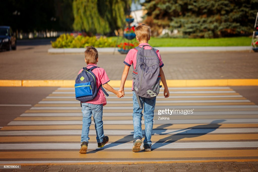 Two brothers  with backpack walking, holding on warm day  on the : Stock Photo
