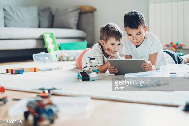 two brothers with digital tablet and plastic blocks lying on the floor - irmão imagens e fotografias de stock