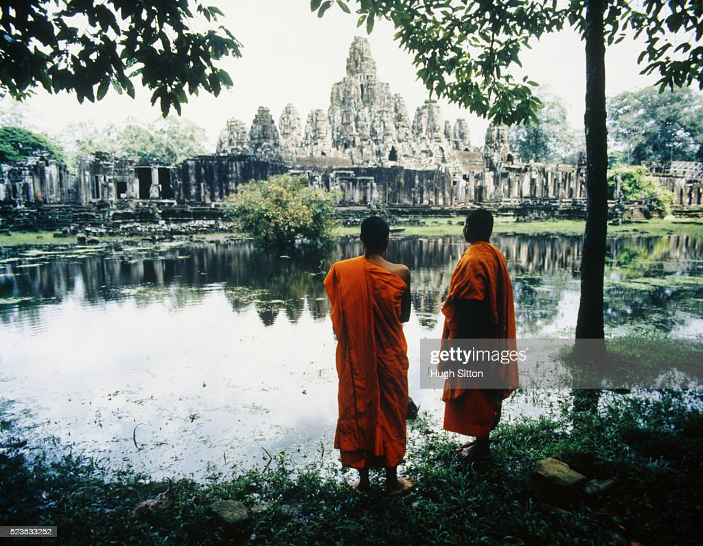 Two Buddhist Monks by Lake Opposite Temple : Stock Photo