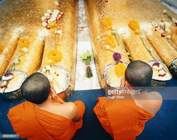 two buddhist monks praying at feet of giant buddha statue - hugh sitton stock pictures, royalty-free photos & images