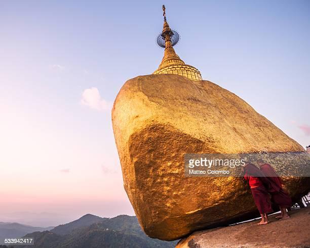 Two buddhist monks praying at golden rock, Myanmar