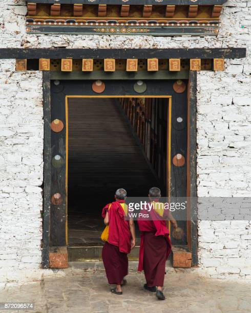 Two Buddhist monks walk into the entryway of the bridge into the Punakha Dzong in Punakha, Bhutan.