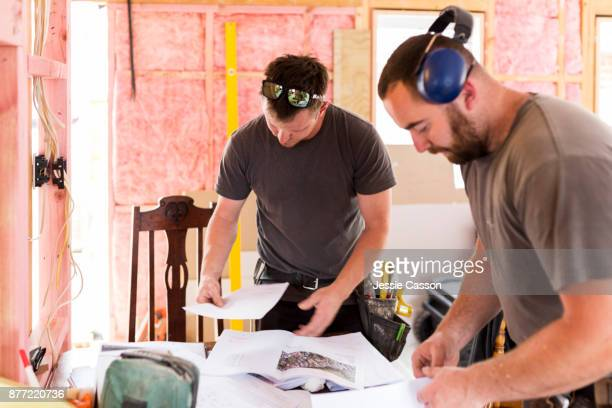 Two builders looks at building plans on construction site
