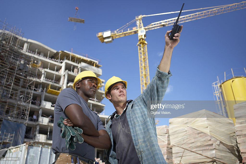 Two Builders on a Building Site, with One Man Pointing with a Walkie Talkie : Stock Photo